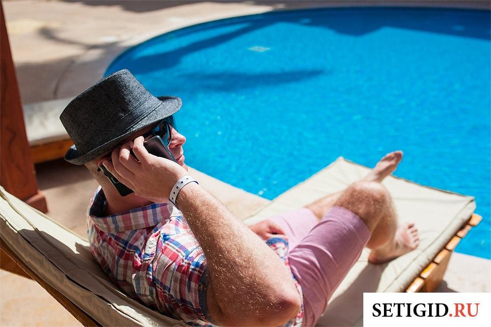 парень с мобильным телефоном у бассейна