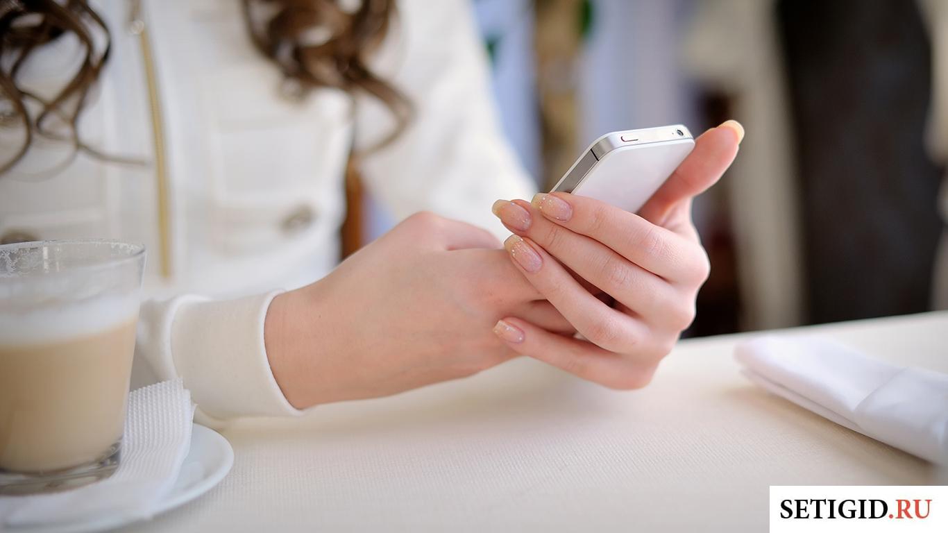 Девушка держит мобильный телефон в руках