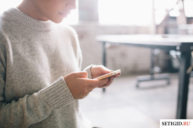 Девушка в белом свитере держит в руках мобильный телефон
