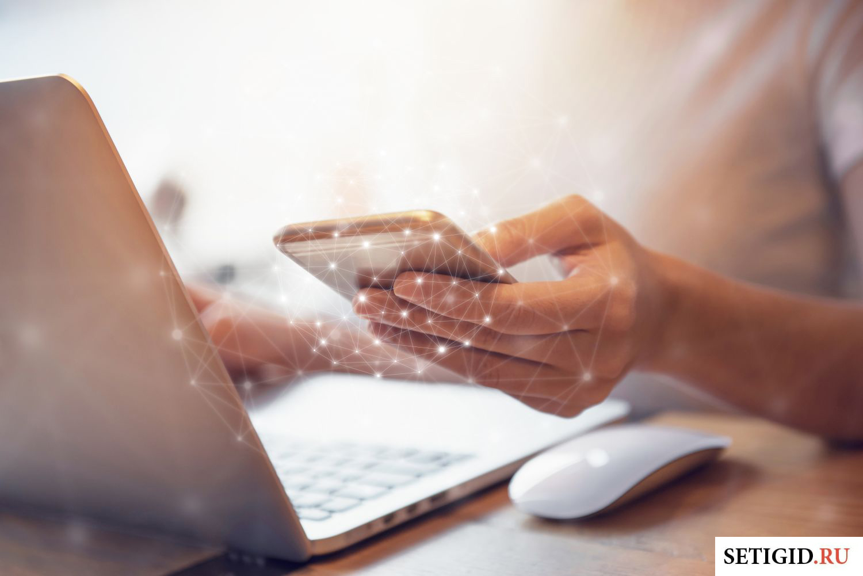 Девушка держит в руке телефон, работая за ноутбуком