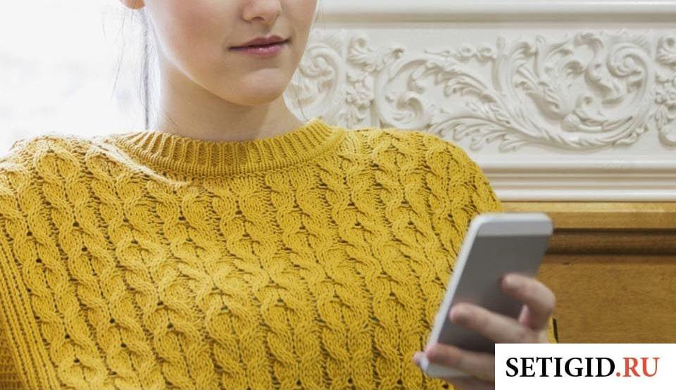 Девушка в желтом свитере держит телефон в руках