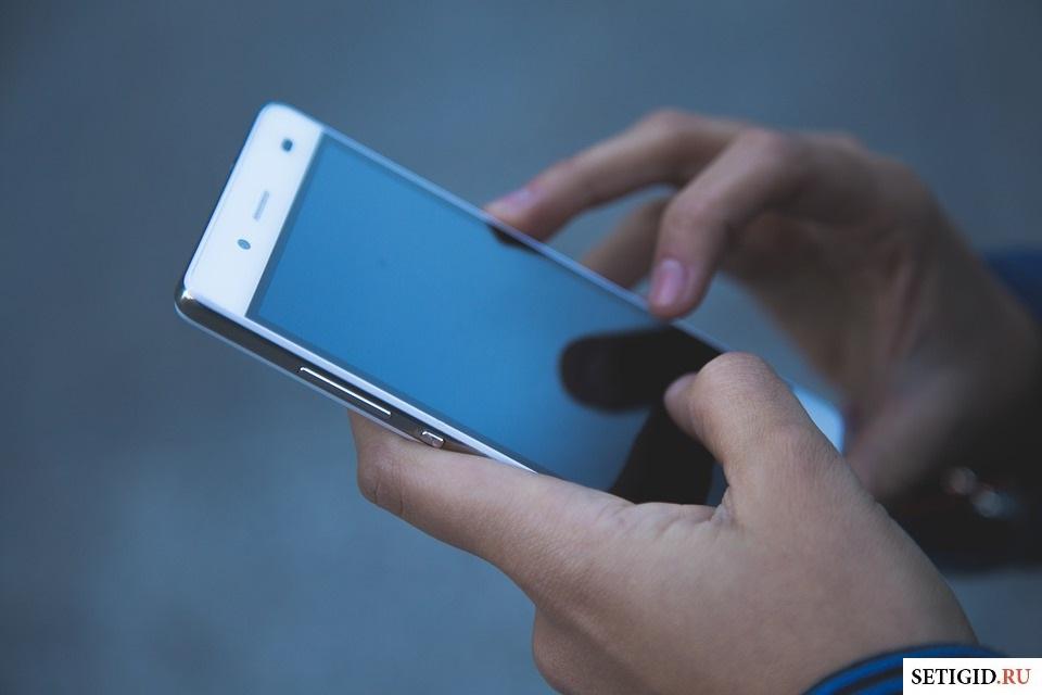Девушка в руках держит мобильный