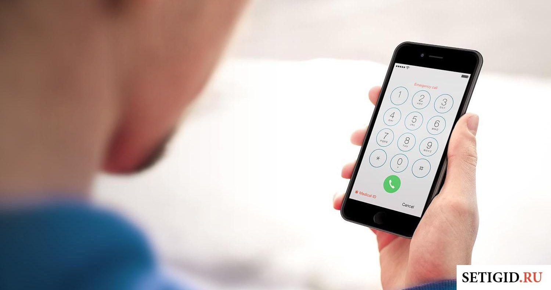 Мужчина набирает номер на мобильном телефоне