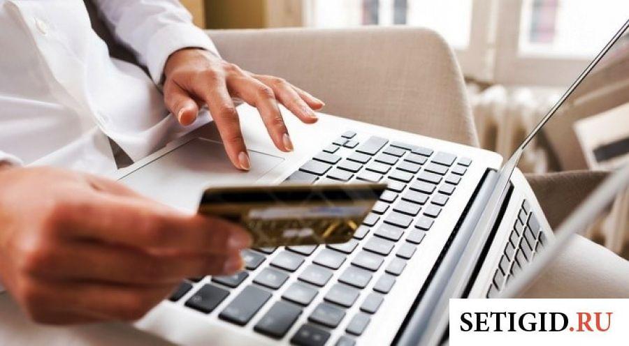 Женщина в белой рубашке сидит за ноутбуком и держит карточку