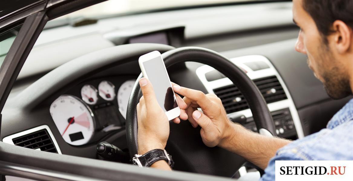 Телефон в руках у мужчины в машине