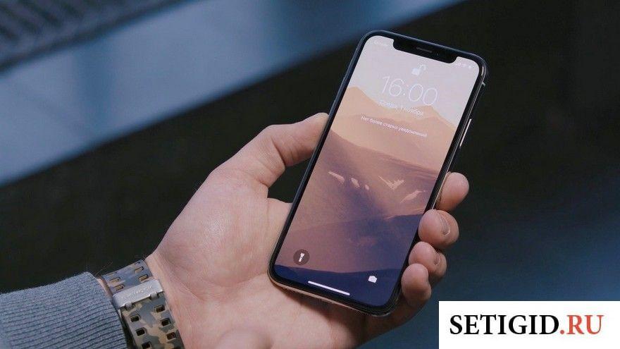 Чёрный телефон в мужских руках на тёмном фоне