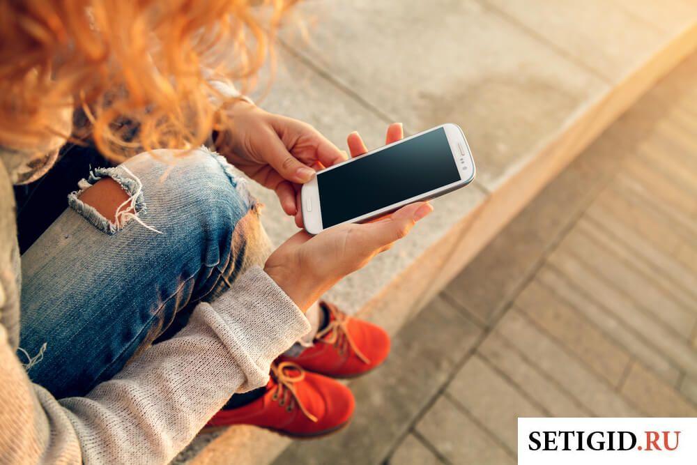 Рыжеволосая девушка с телефоном в руках