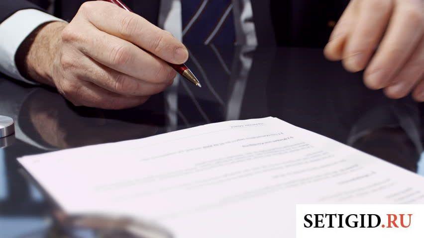 Мужчина в костюме с ручкой в руках пишет