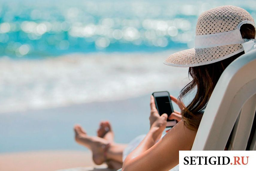 Девушка на море в белой шляпе с телефоном в руках