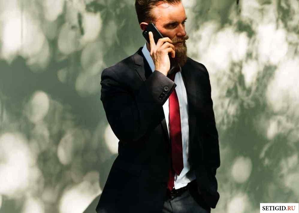 Мужчина в костюме разговаривает по телефону