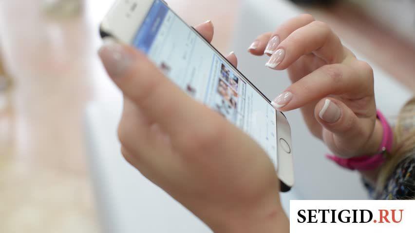 Белый телефон в руке у девушки с накрашенными ногтями