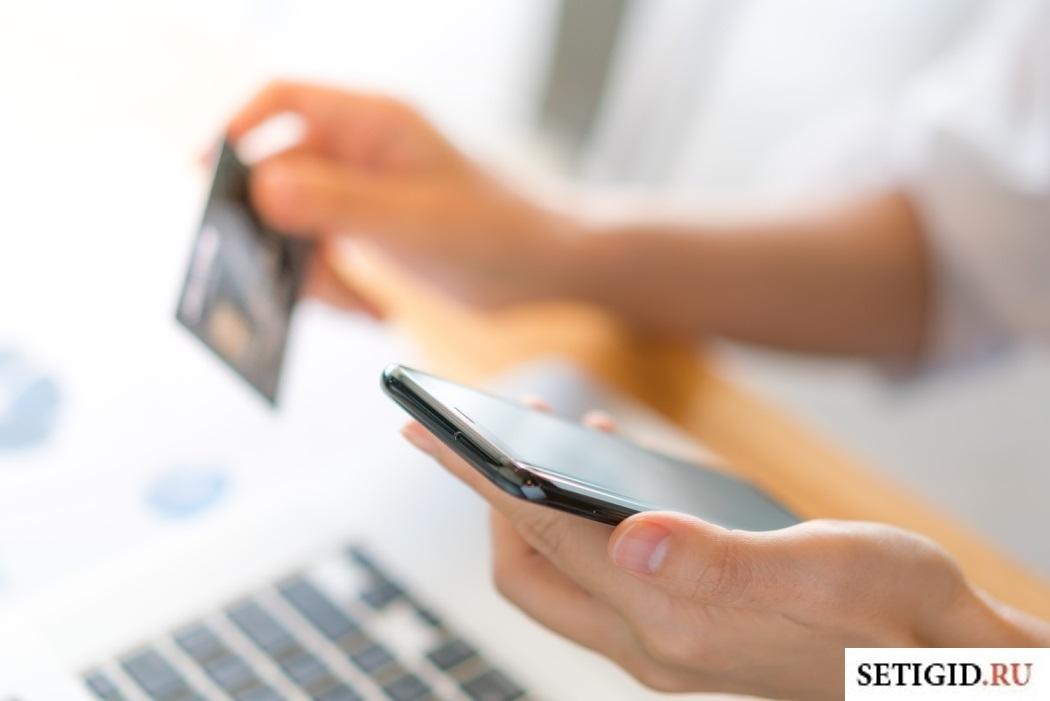 Девушка переводит деньги с телефона на карту