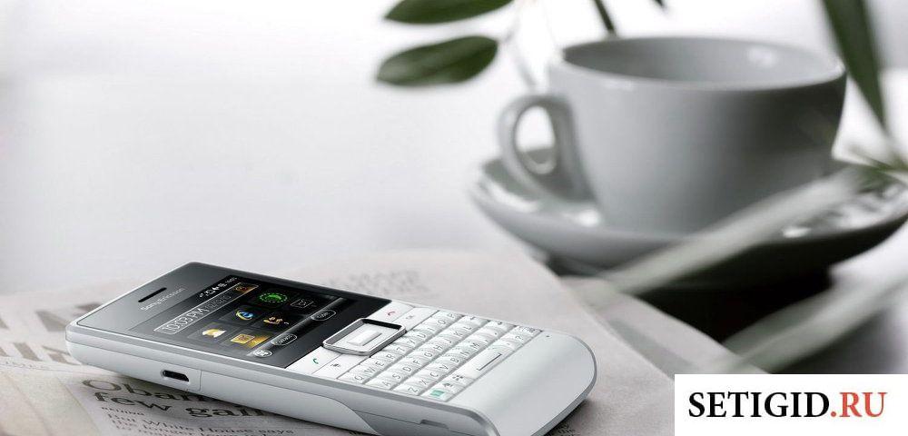 Белая чашка и белый телефон с чёрным экраном лежат на столе