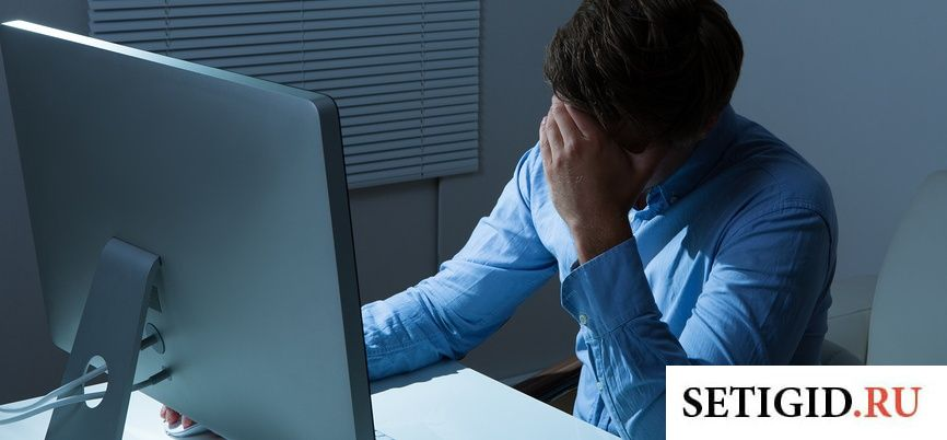 Мужчина в голубой рубашке сидит за компьютером и держится за голову
