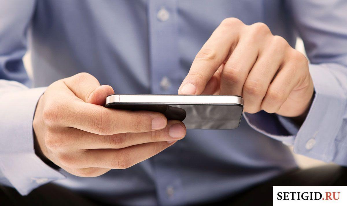 Телефон в руках у мужчины в голубой рубашке