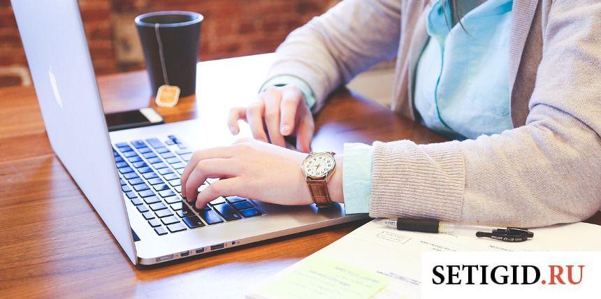 Мужчина в белой кофте и голубой рубашке сидит за ноутбуком