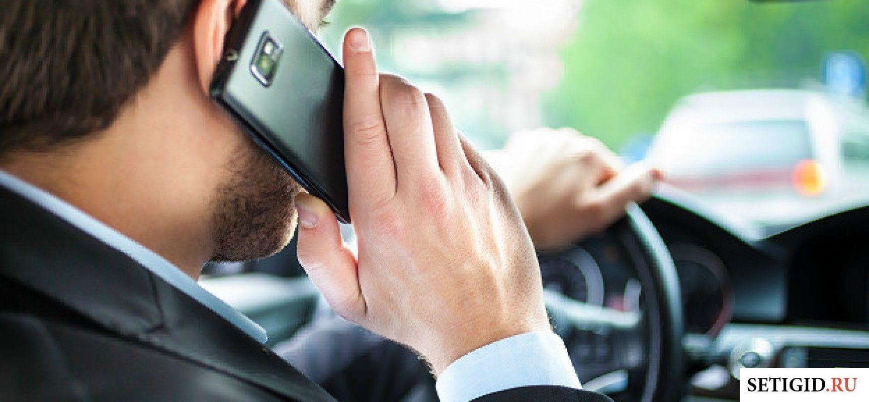Мужчина за рулём разговаривает по мобильному телефону
