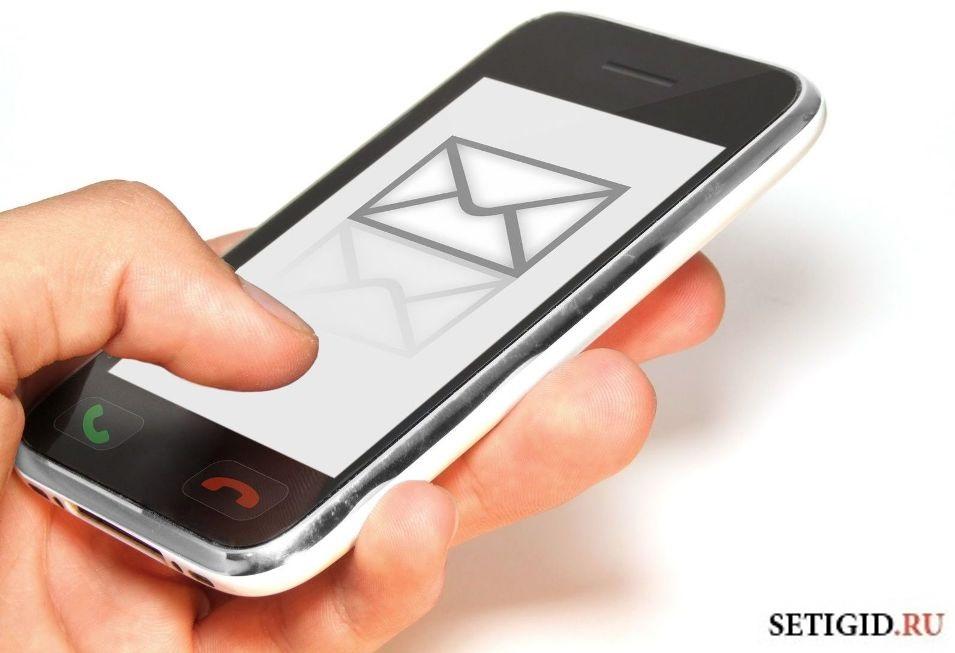 Палец набирает смс на телефоне