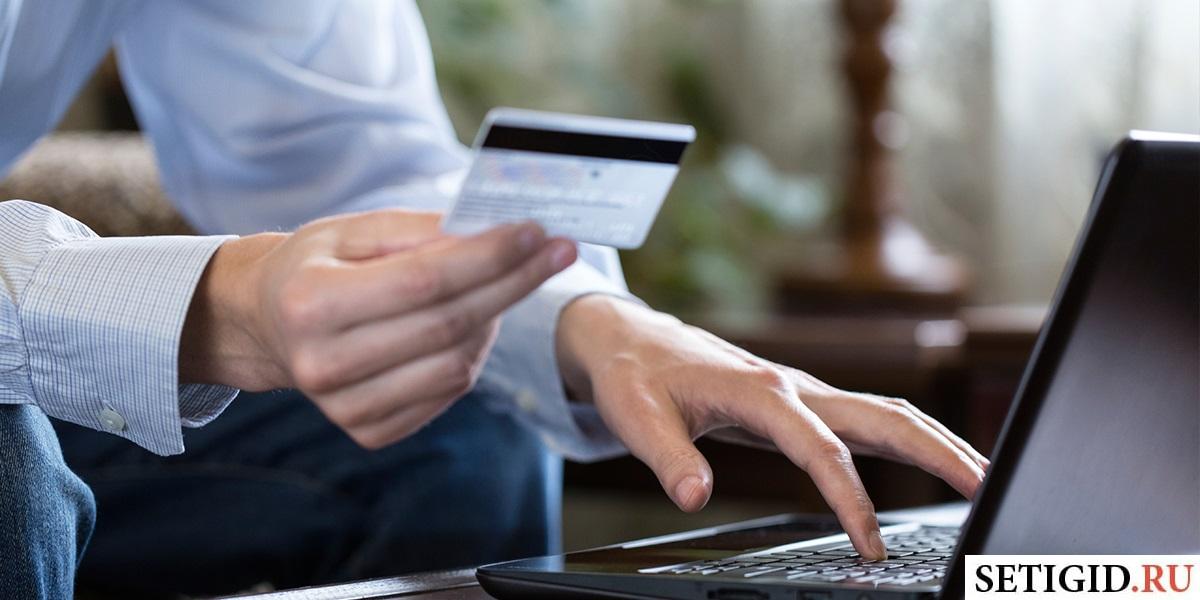 Мужчина делает перевод с банковской карты с помощью компьютера