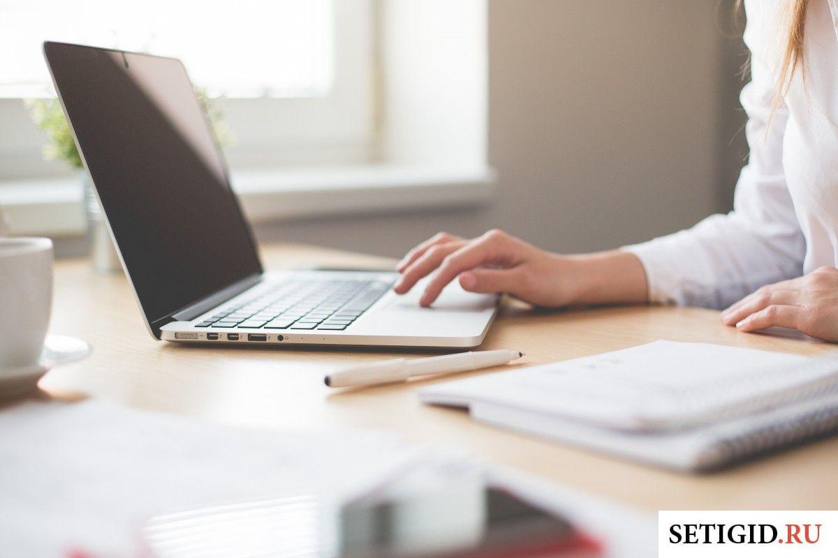 Женщина сидит в ноутбуке за письменным столом