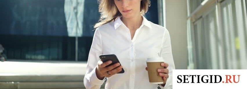 Девушка в белой рубашке смотрит в телефон