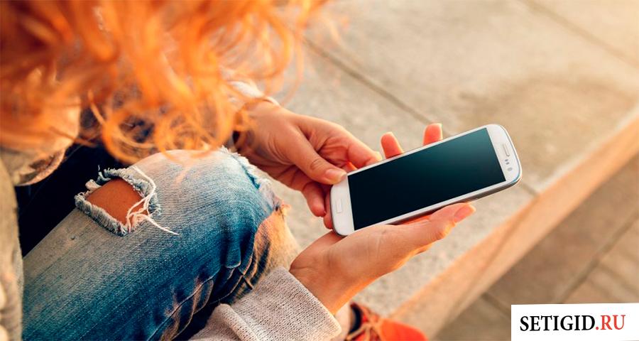 Держит в женской руке смартфон