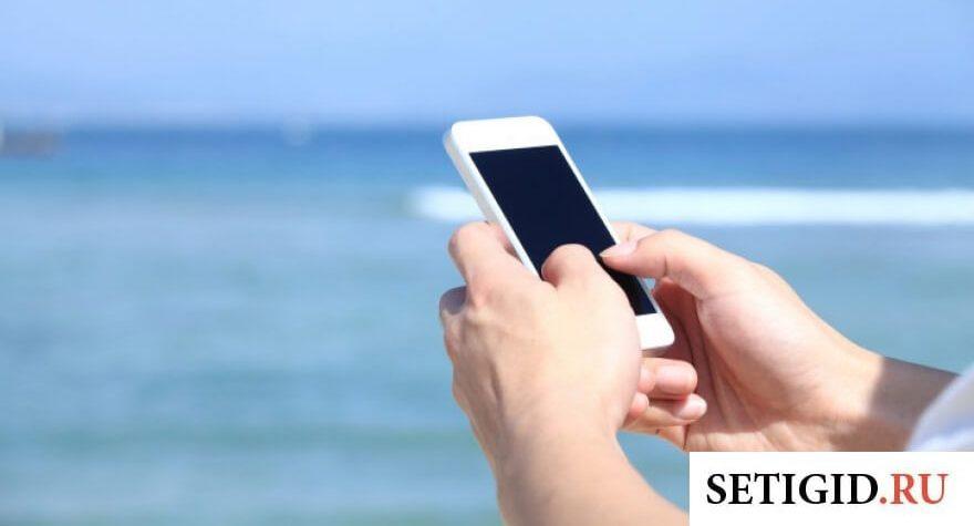 Белый телефон на фоне моря