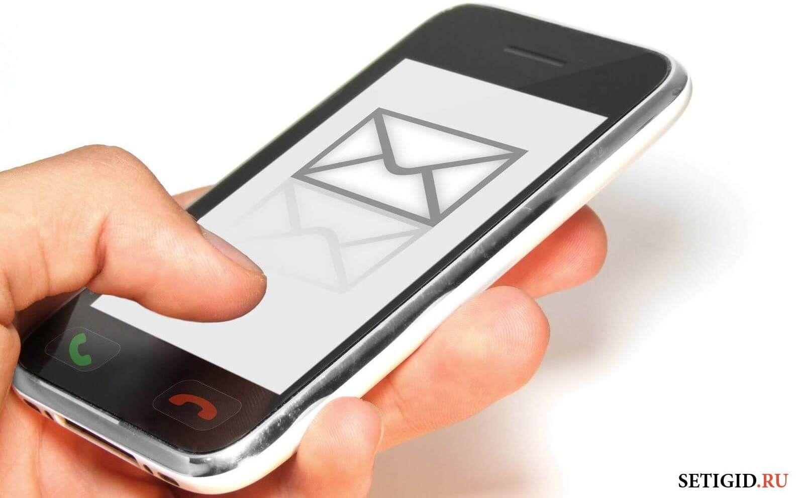 Белый телефон в руке с сообщением на экране