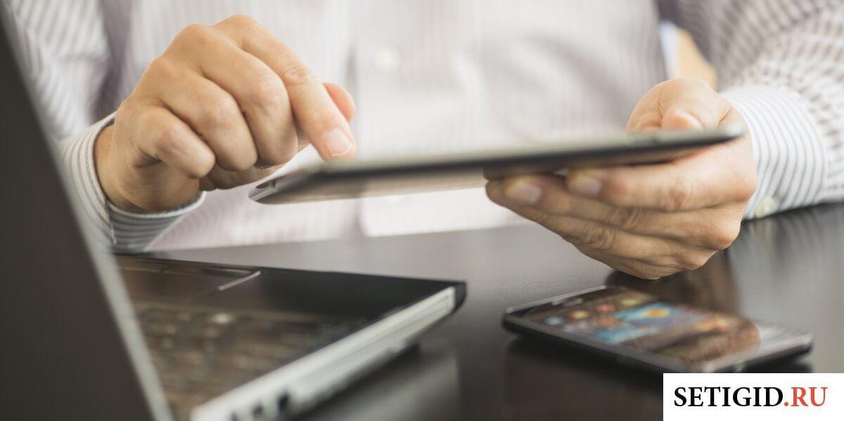 Человек в белой рубашке, держащий в руках планшет