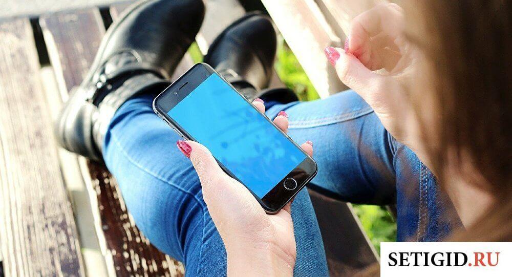 Девушка в джинсах, держащая чёрный телефон в руках