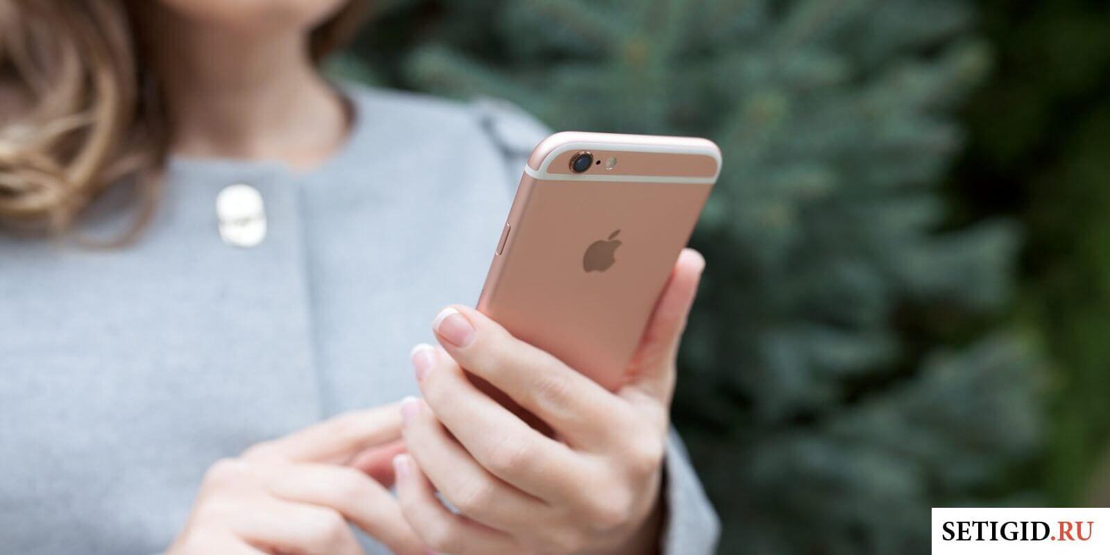 Девушка в серой кофте, держащая телефон в руках