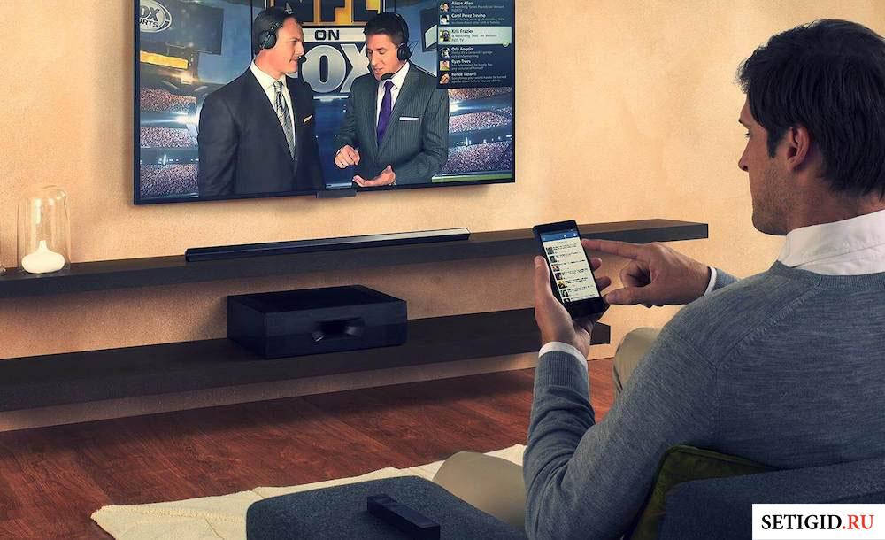 Мужчина с телефоном в руках, смотрящий телевизор