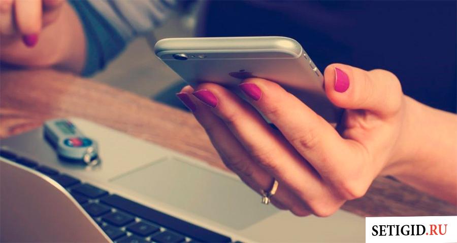 Смартфон в женской руке над ноутбуком