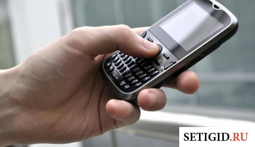 Маленький телефон в руке у мужчины около окна