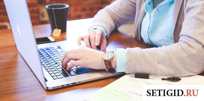 Мужчина с часами на руках, работающий за ноутбуком