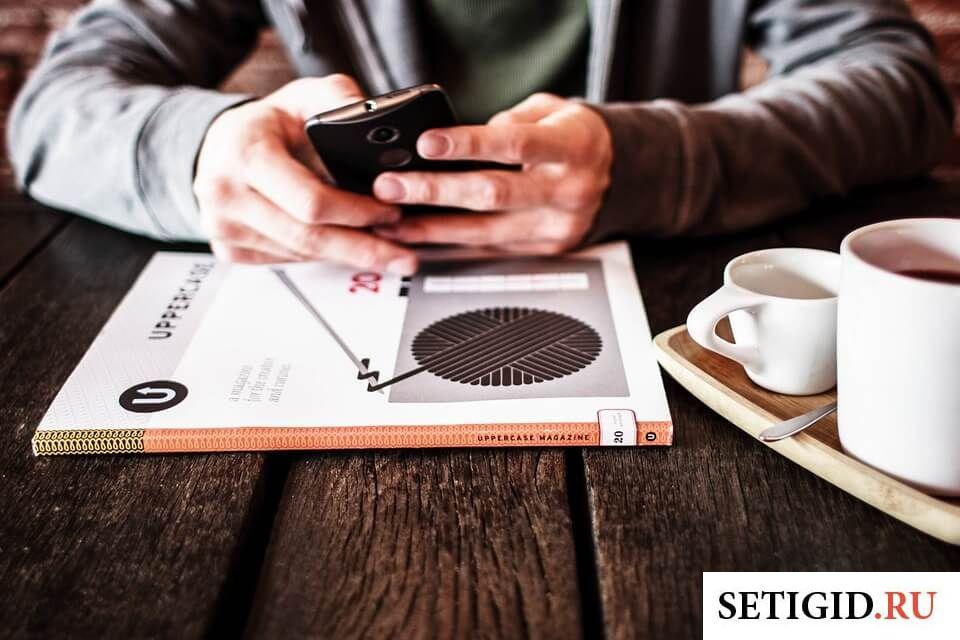 Мужчина, сидящий за рабочим столом с телефоном