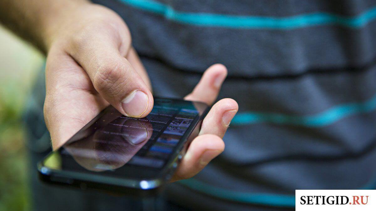 Мужчина в полосатой кофте с телефоном