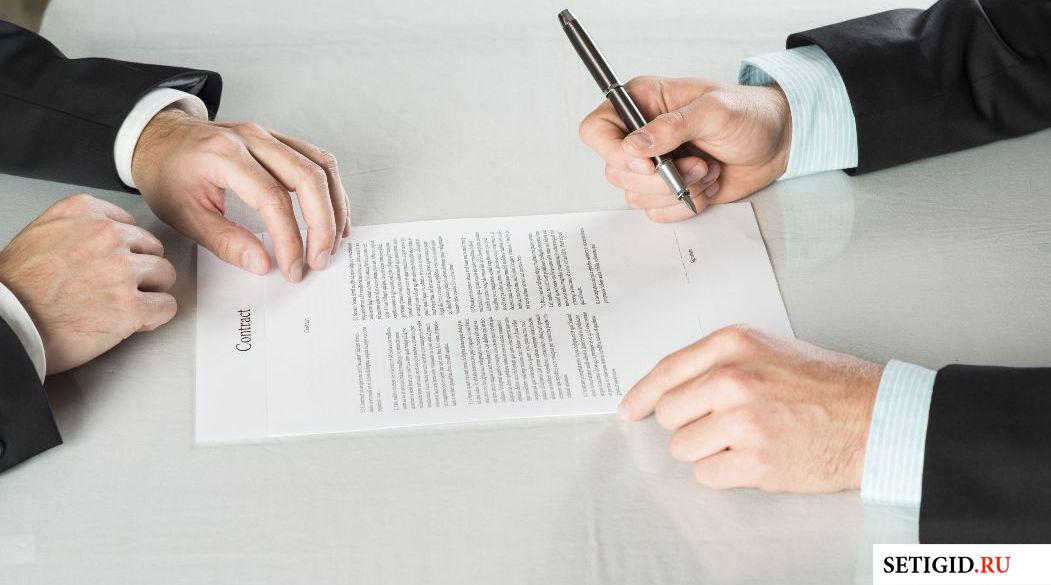 Мужчина подписывающий договор