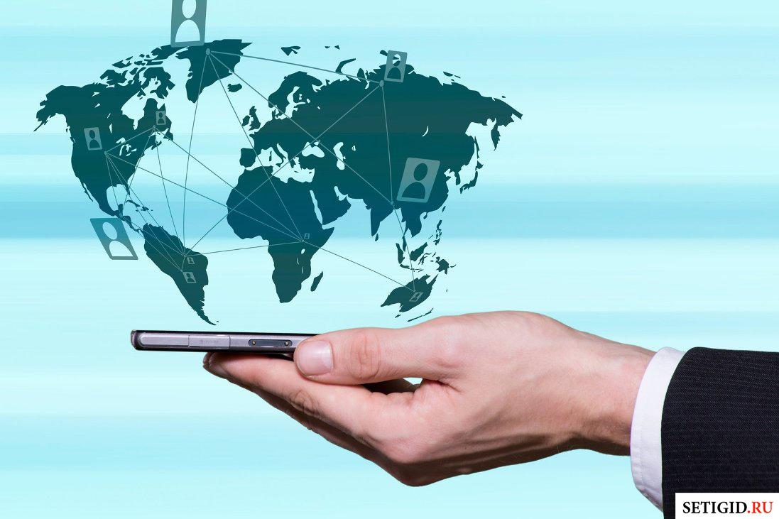 Проекция карты мира над смартфоном в мужской руке