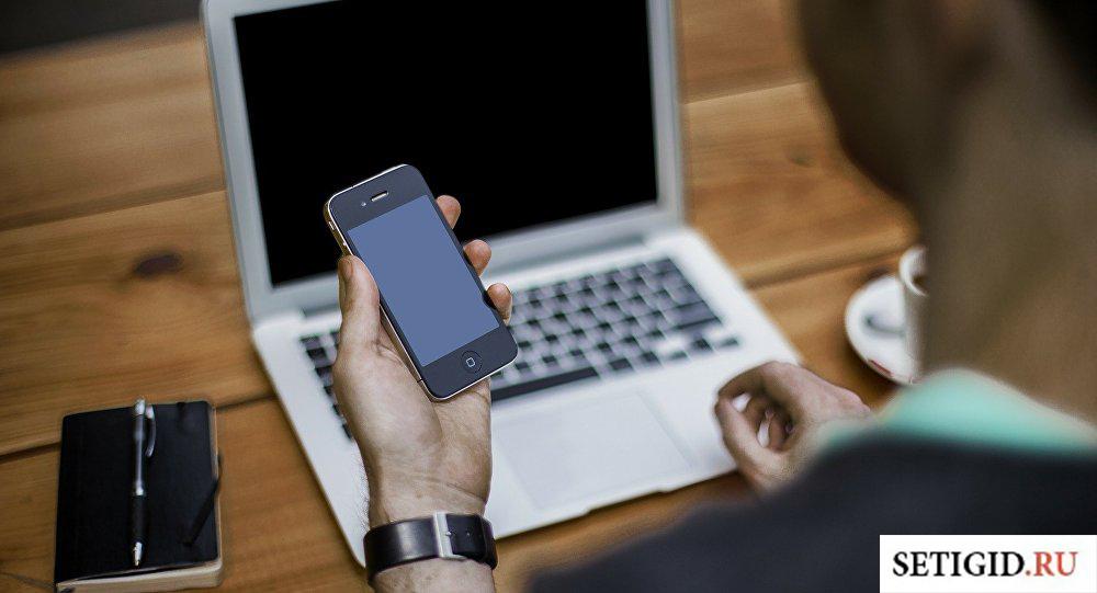 Мужчина держит выключенный смартфон над ноутбуком