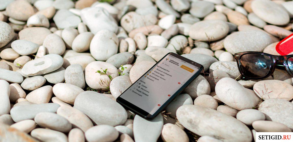 Включенный смартфон, лежащий на гальке