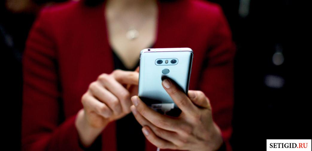 Женщина, держащая телефон в руках