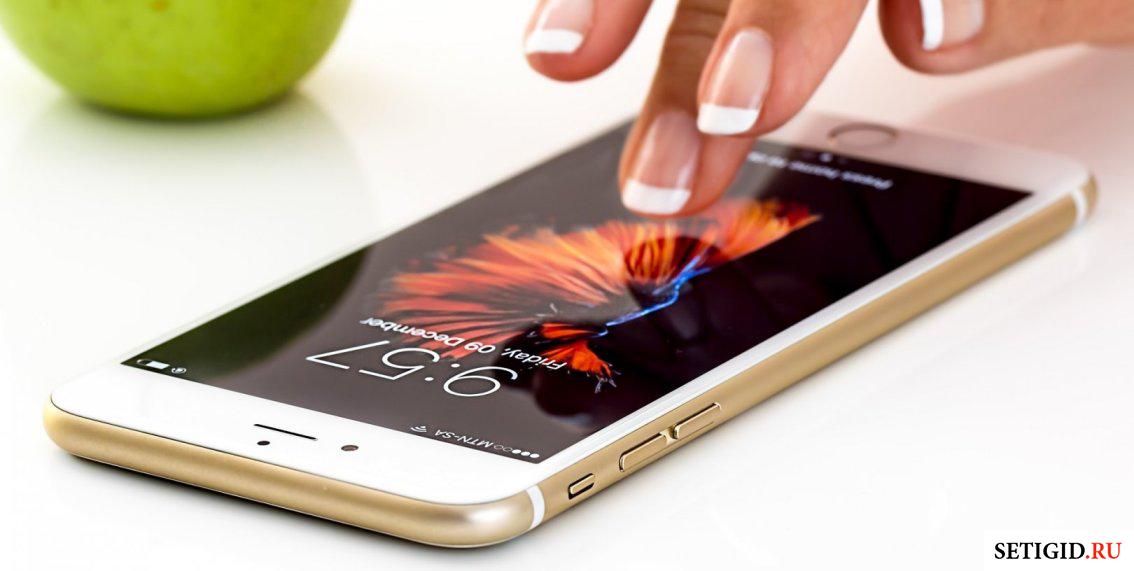 Рука над смартфоно на столе