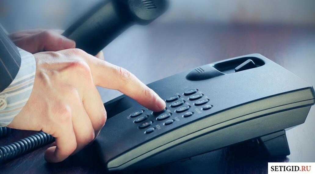 Мужская рука на стационарном телефоне