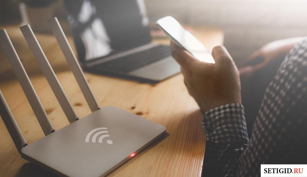 Человек, сидящий за столом с ноутбуком и роутером