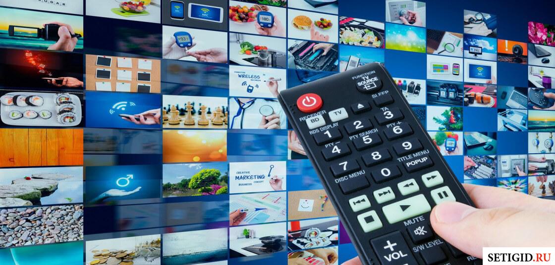 Пульт управления на фоне заставок каналов цифрового телевидения