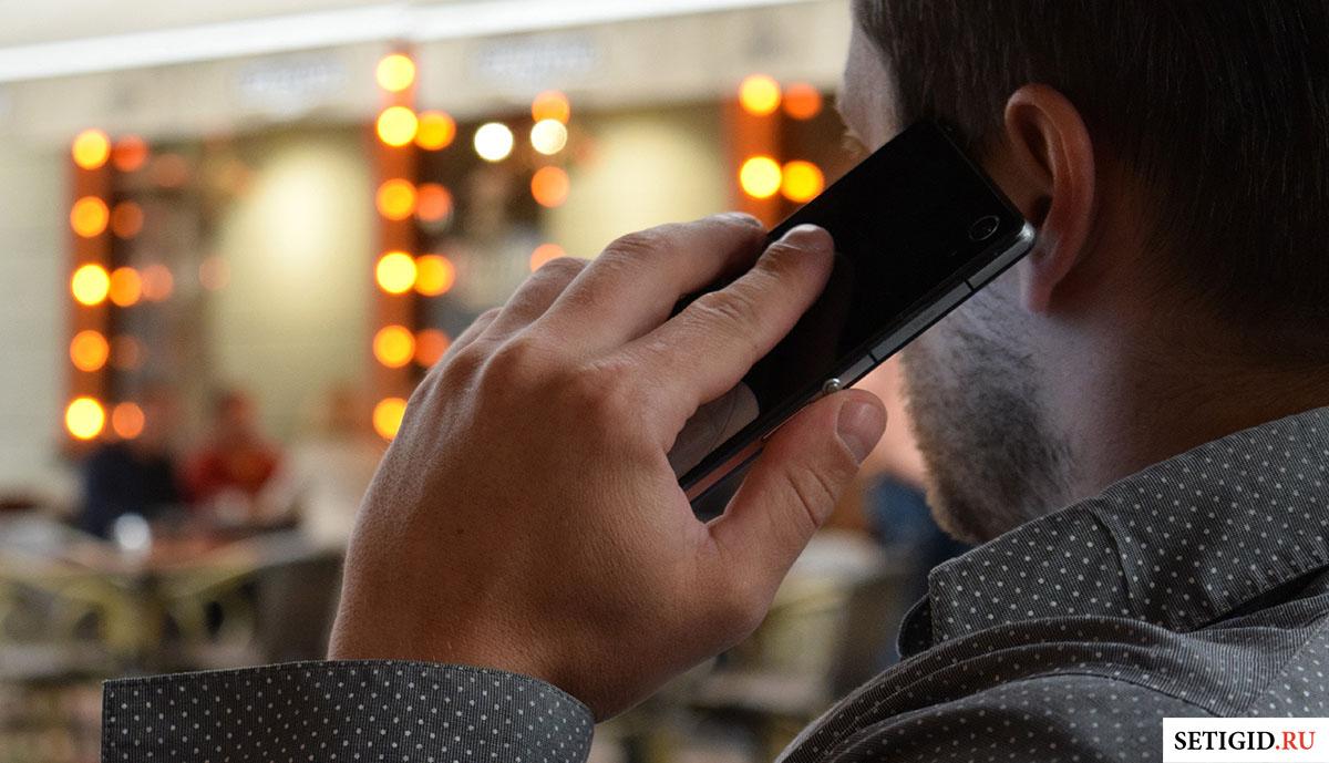 Мужчина, разговаривающий по мобильному телефону